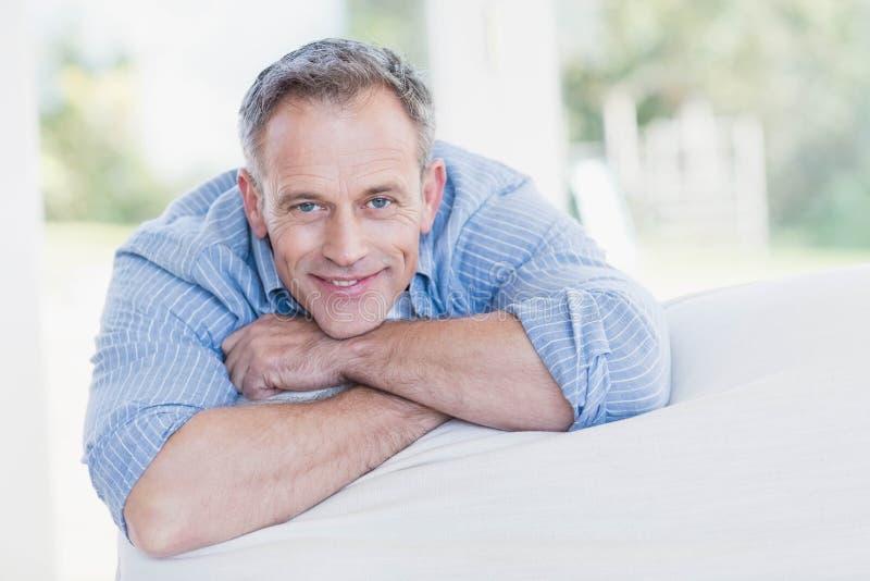 Homem feliz que relaxa no sofá imagens de stock