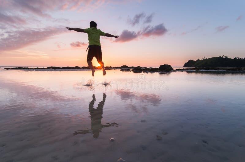 Homem feliz que salta na água fotografia de stock royalty free