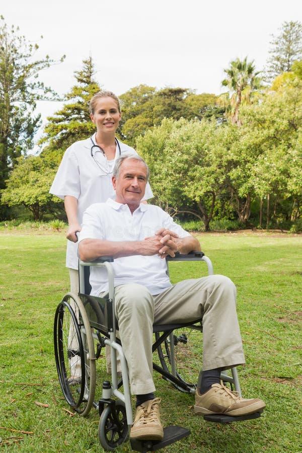 Homem feliz que senta-se em uma cadeira de rodas com sua enfermeira que empurra o fotos de stock