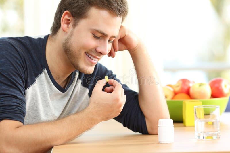 Homem feliz que toma um comprimido da vitamina em casa fotografia de stock royalty free