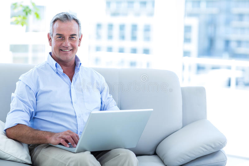 Homem feliz que trabalha no portátil em casa foto de stock