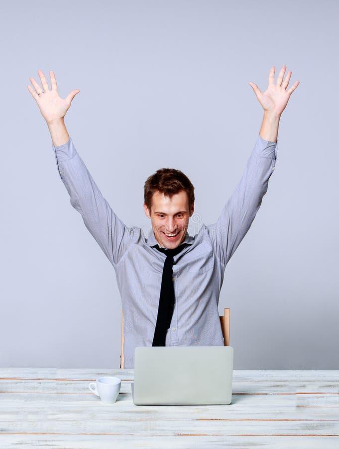 Homem feliz que trabalha no portátil no escritório fotografia de stock