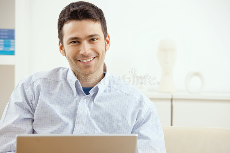 Homem feliz que usa o portátil