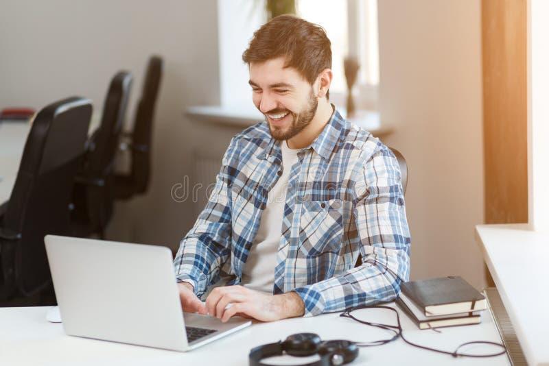 Homem feliz que usa o portátil na tabela no escritório imagem de stock