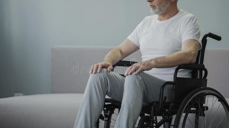 Homem ferido na cadeira de rodas no centro de reabilitação, esperanças andar outra vez, close up imagem de stock