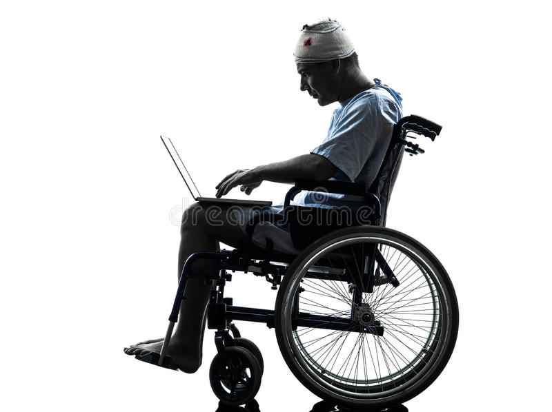 Homem ferido na silhueta de computação do computador portátil da cadeira de rodas foto de stock royalty free