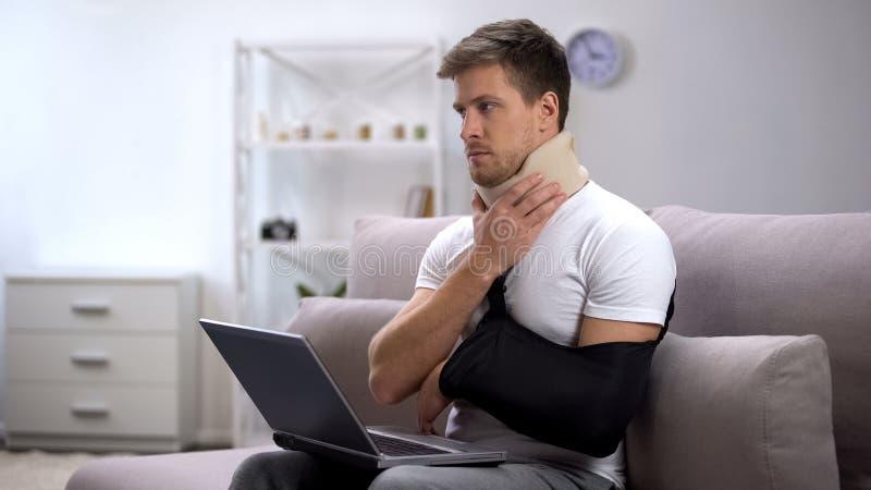 Homem ferido no colar cervical da espuma e no estilingue do braço que trabalham na dor de sentimento do portátil imagens de stock royalty free