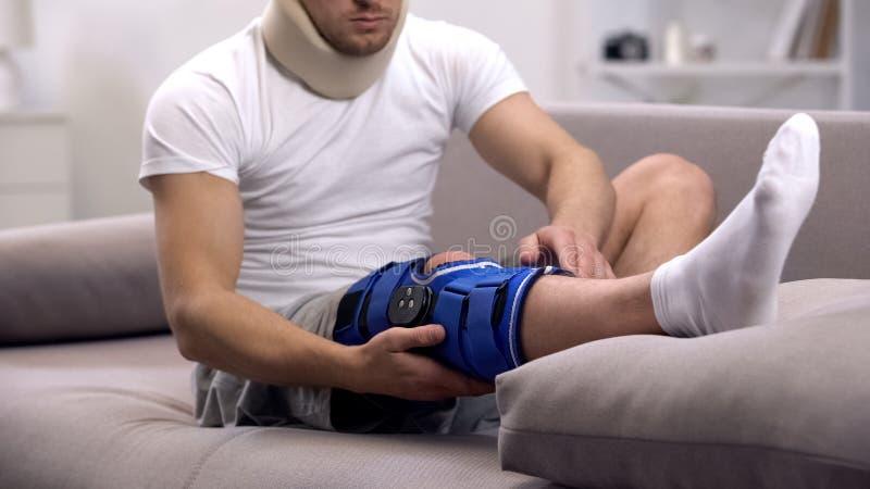 Homem ferido no colar cervical da espuma que verifica a cinta de joelho do neopreno, reabilitação imagens de stock