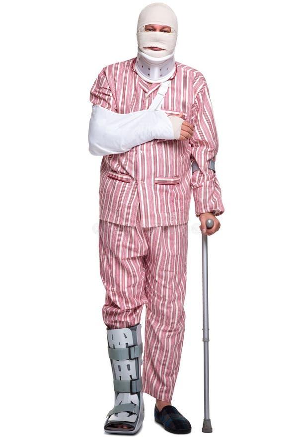 Homem ferido que anda na parte dianteira das muletas imagem de stock