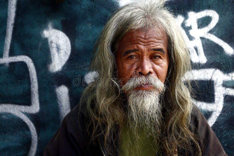 Homem filipino superior com cabeça e pêlos faciais cinzentos imagens de stock