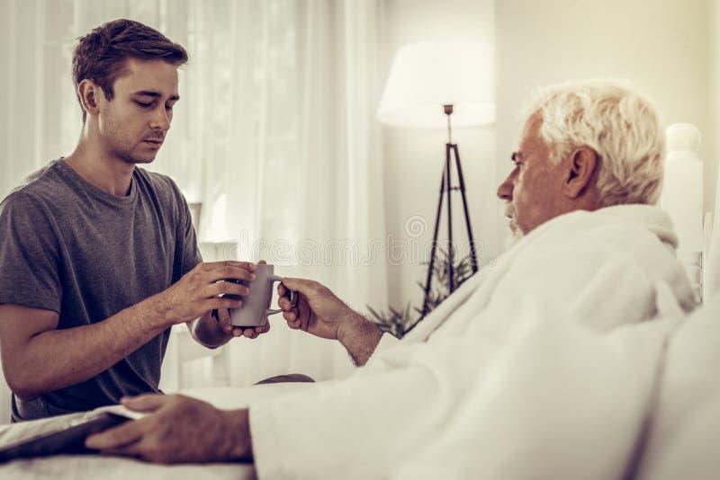 Homem focalizado que passa o copo ao pai doente na cama foto de stock