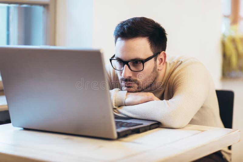 Homem forçado ao trabalhar no portátil fotografia de stock royalty free