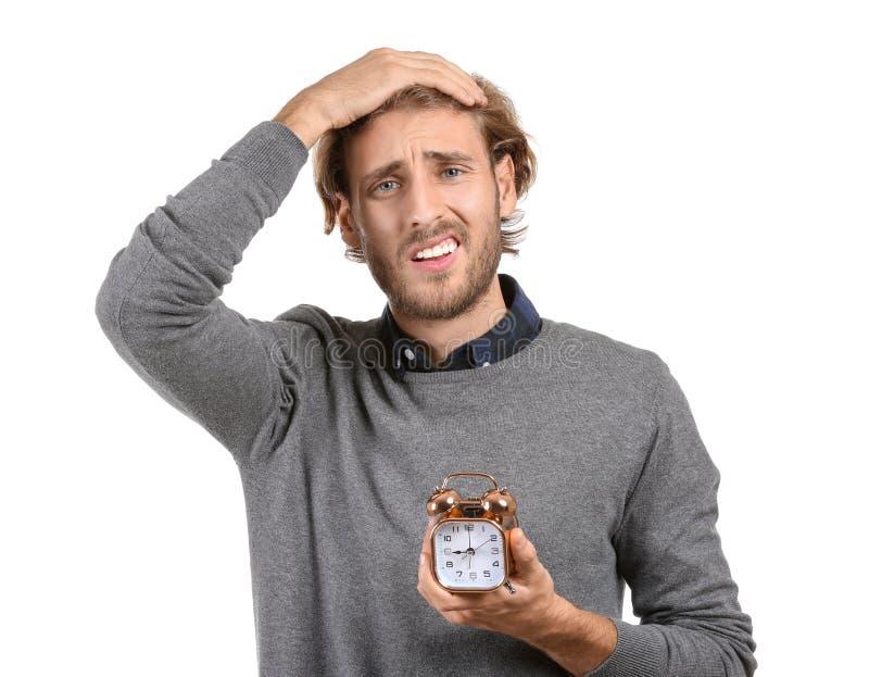 Homem forçado com o despertador no fundo branco fotos de stock royalty free