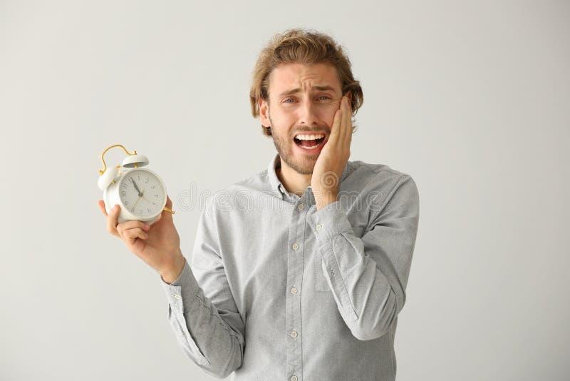 Homem forçado com o despertador no fundo claro fotografia de stock