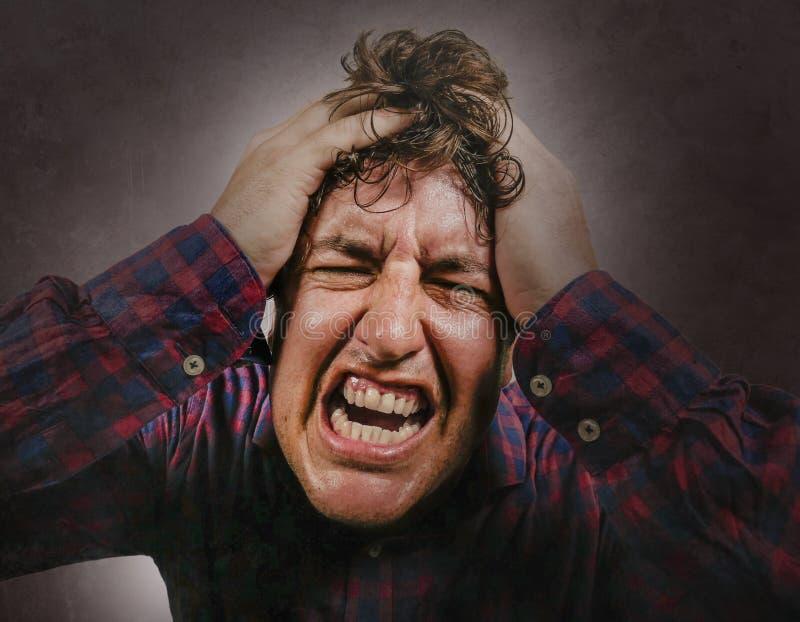 Homem forçado e oprimido que grita e que puxa o cabelo no esforço louco e na expressão frustrante da cara que olham para a câmera imagem de stock