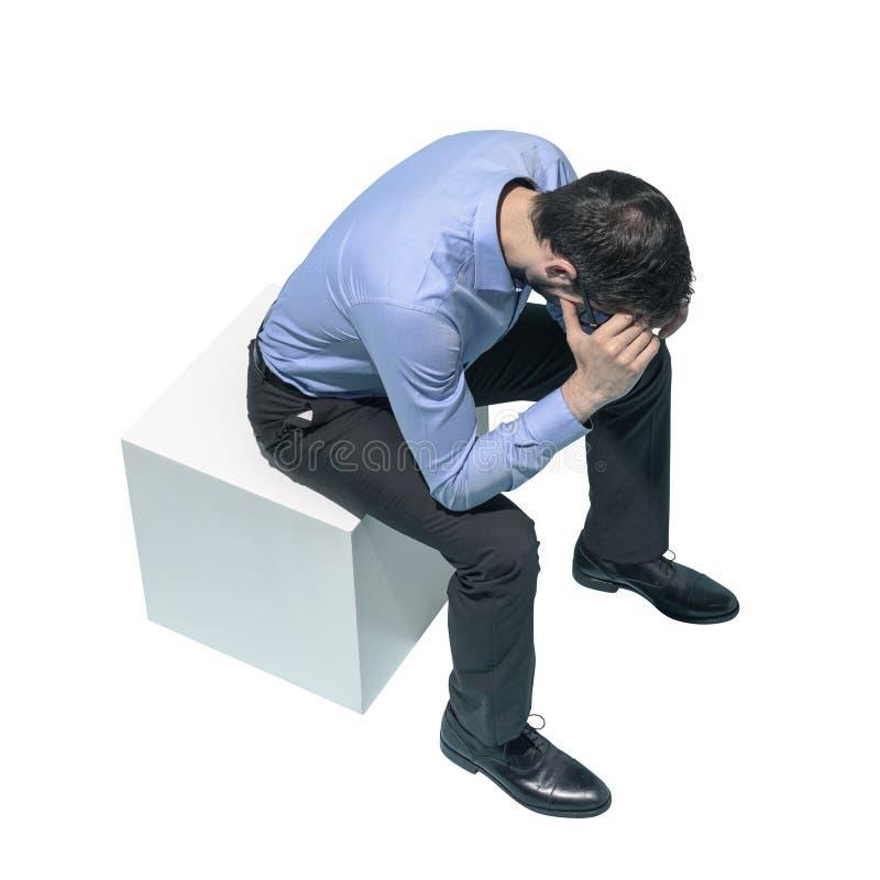 Homem forçado que senta-se com cabeça nas mãos fotos de stock royalty free