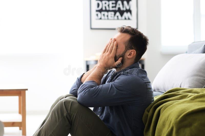 Homem forçado que senta-se no assoalho em casa fotos de stock