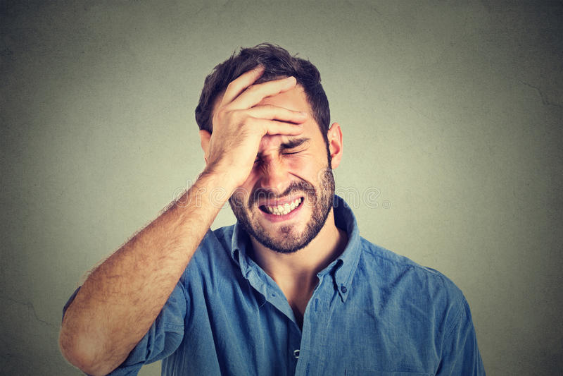 Homem forçado que sofre da dor de cabeça isolada no fundo cinzento da parede fotografia de stock royalty free