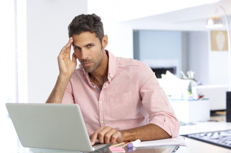 Homem forçado que trabalha no portátil no escritório domiciliário fotografia de stock royalty free
