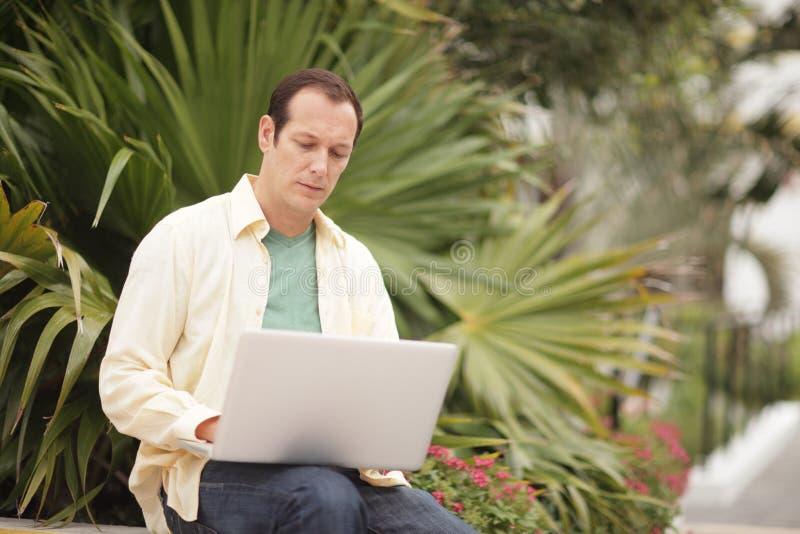 Homem fora com um computador portátil imagem de stock royalty free