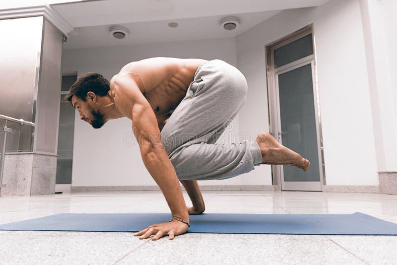 Homem forte atlético que pratica a pose difícil da ioga imagem de stock royalty free