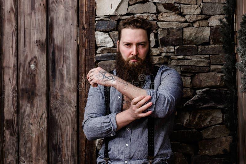 Homem forte brutal com uma barba e tatuagens em suas m?os vestidas em suportes ? moda da roupa ocasional no fundo de imagens de stock royalty free