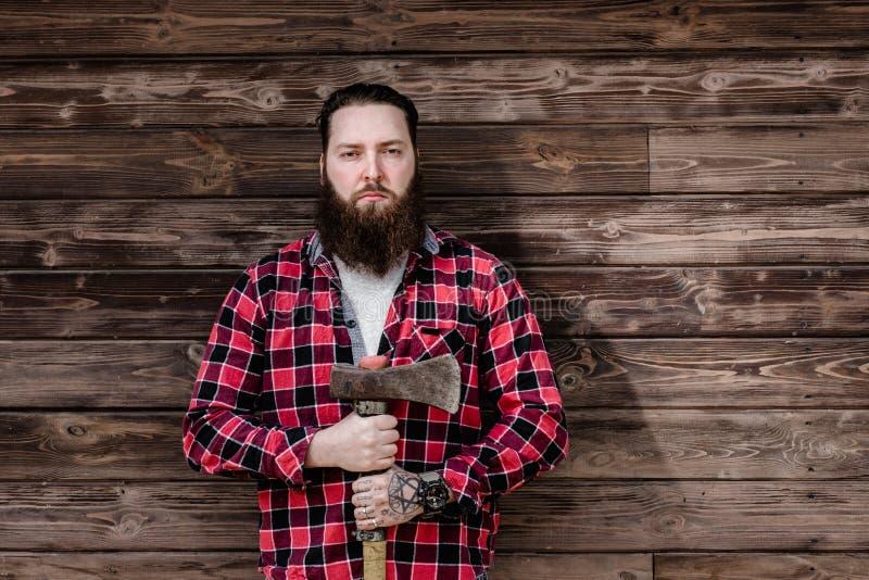 Homem forte brutal com uma barba vestida em uma camisa verificada e em uns suportes rasgados das calças de brim com um machado na foto de stock royalty free