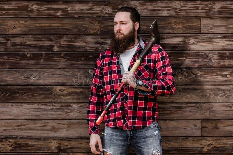 Homem forte brutal com uma barba vestida em uma camisa verificada e em uns suportes rasgados das cal?as de brim com um machado na imagens de stock