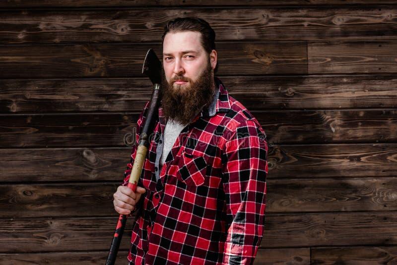 Homem forte brutal com uma barba vestida em uma camisa verificada e em uns suportes rasgados das cal?as de brim com um machado na imagem de stock