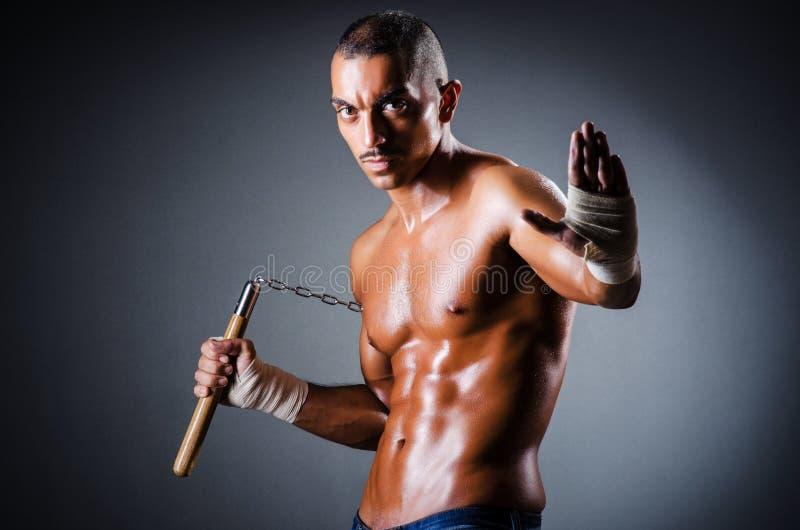 Homem forte com nunchaku fotos de stock