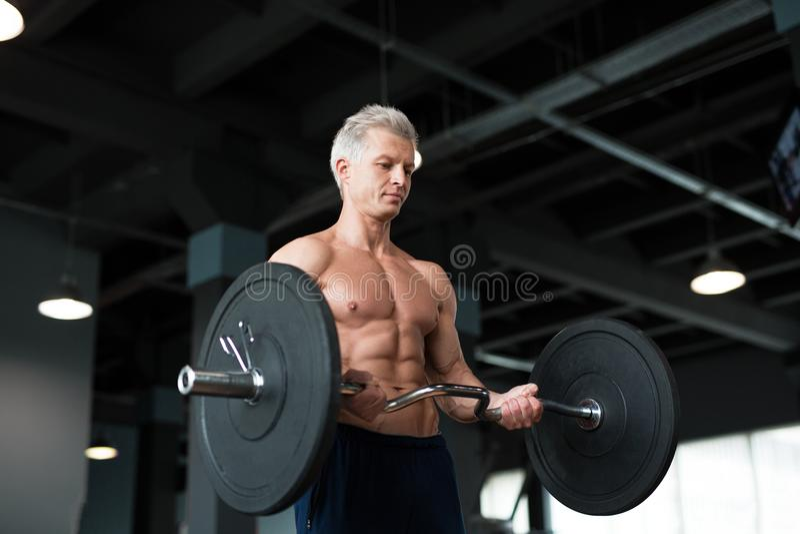 Homem forte com o corpo muscular que dá certo no gym Exercício do peso com o barbell no clube de aptidão foto de stock