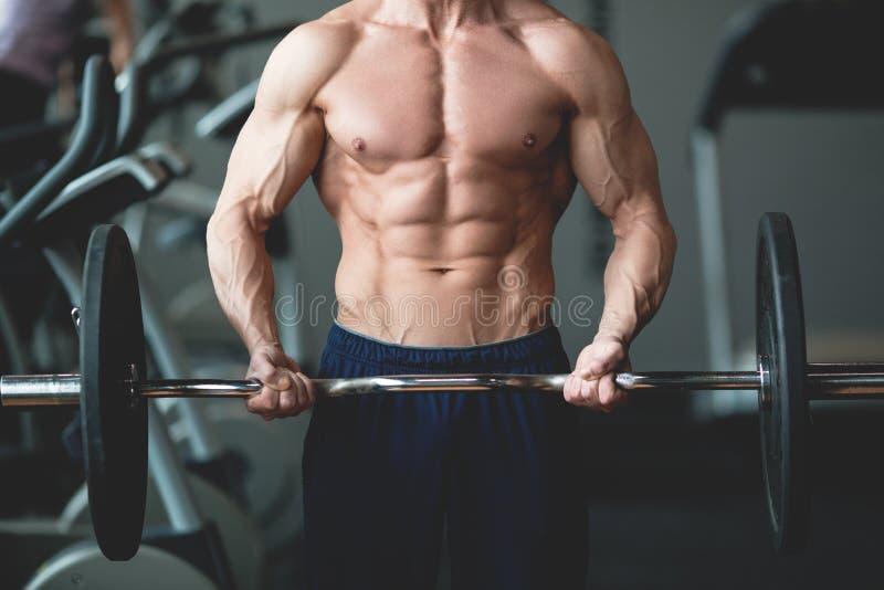 Homem forte com o corpo muscular que dá certo no gym Exercício do peso com o barbell no clube de aptidão Imagem tonificada imagens de stock royalty free