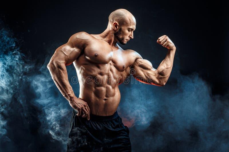 Homem forte do halterofilista com Abs perfeito, ombros, bíceps, tríceps, caixa foto de stock royalty free
