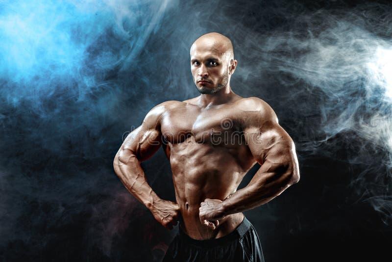 Homem forte do halterofilista com Abs perfeito, ombros, bíceps, tríceps, caixa imagem de stock