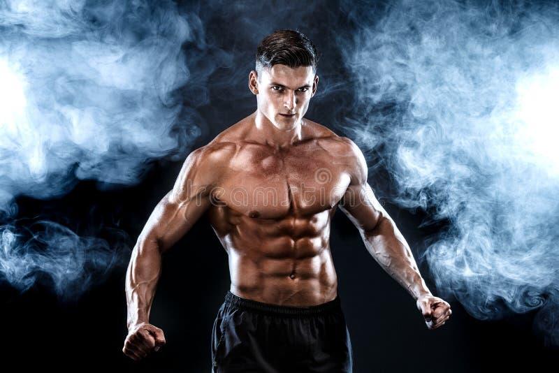 Homem forte do halterofilista com Abs perfeito, ombros, bíceps, tríceps, caixa imagens de stock royalty free