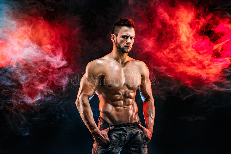 Homem forte do halterofilista em calças militares com Abs perfeitos, ombros, bíceps, tríceps, caixa imagens de stock