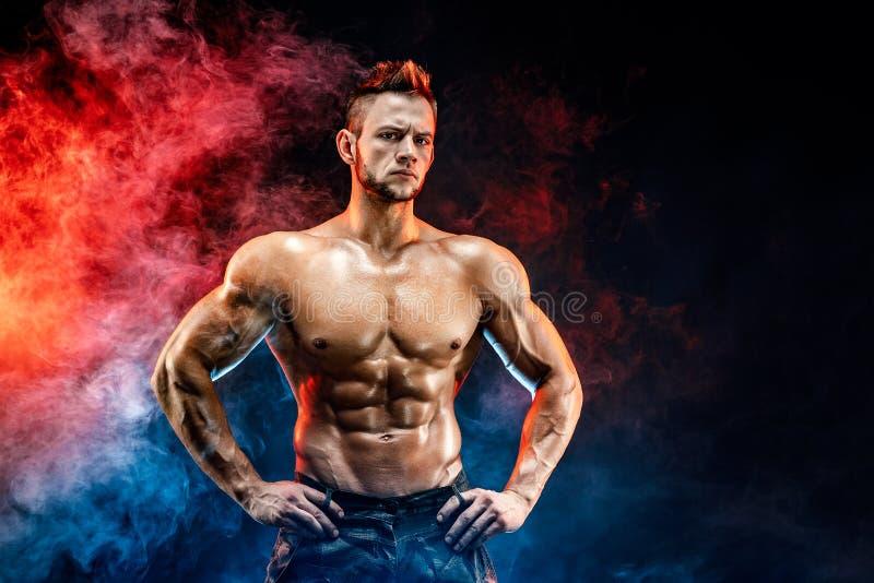 Homem forte do halterofilista em calças militares com Abs perfeitos, ombros, bíceps, tríceps, caixa foto de stock royalty free