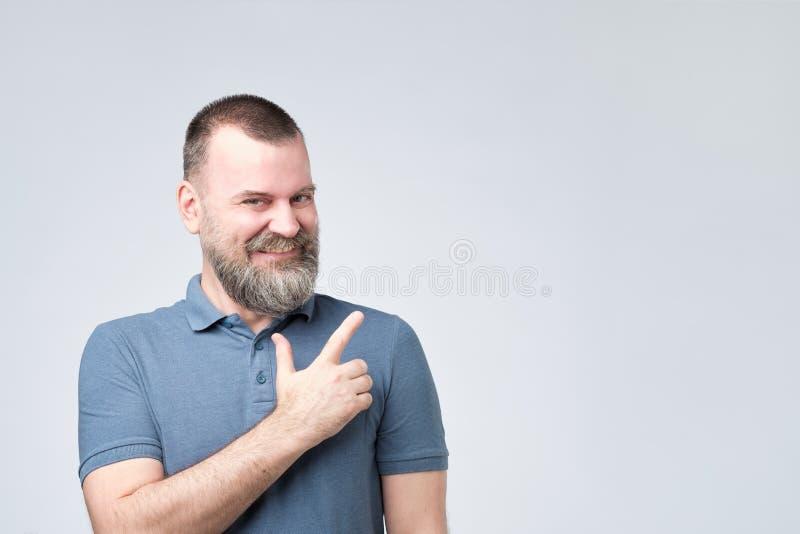 Homem forte maduro com a barba na camisa azul que aponta um lado com expressão surpreendida da cara imagem de stock