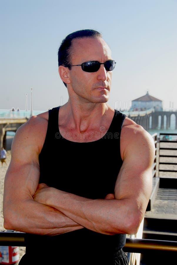 Homem forte na praia imagem de stock royalty free