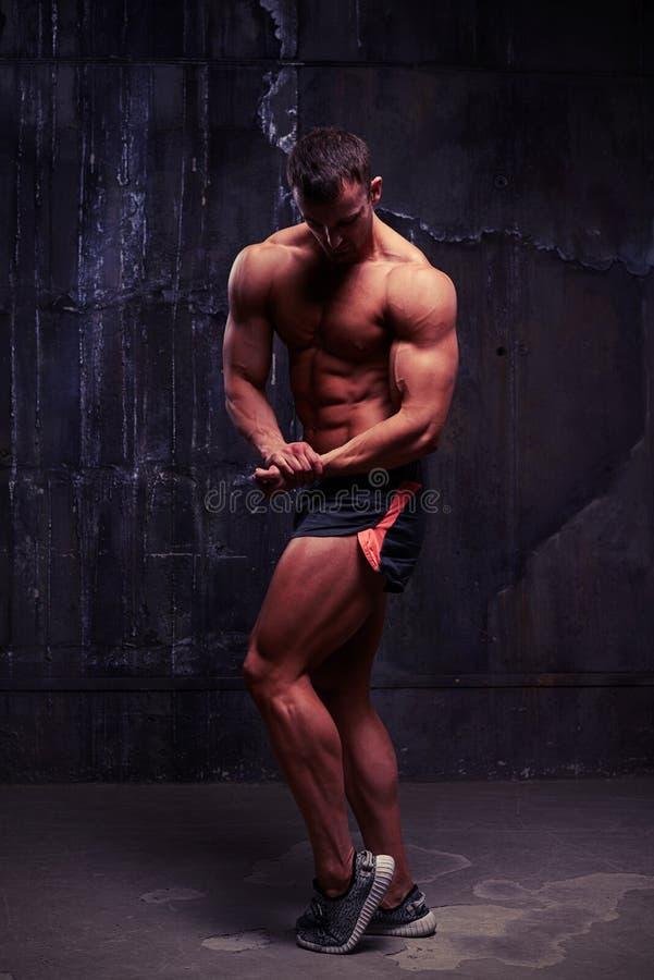 Homem forte no short do esporte com o torso desencapado que dobra os músculos na AR fotos de stock royalty free
