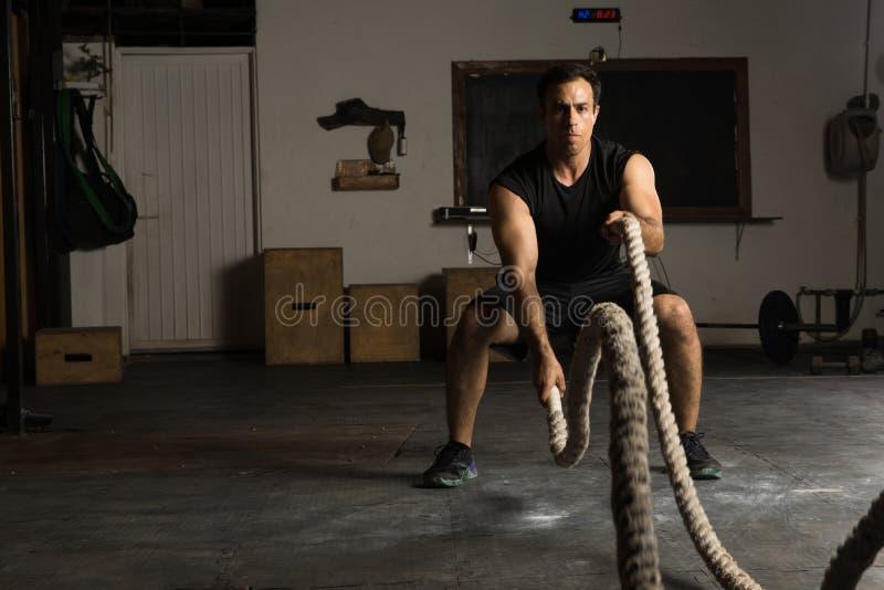 Homem forte que exercita com cordas da batalha imagens de stock