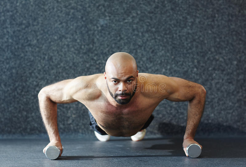 Homem forte que levanta em pesos com esforço fotografia de stock royalty free