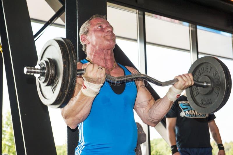 Homem forte que levanta um barbell pesado fotografia de stock