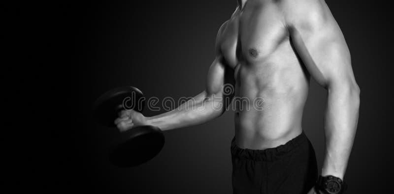 Homem forte que trabalha no clube de aptidão do gym fotografia de stock