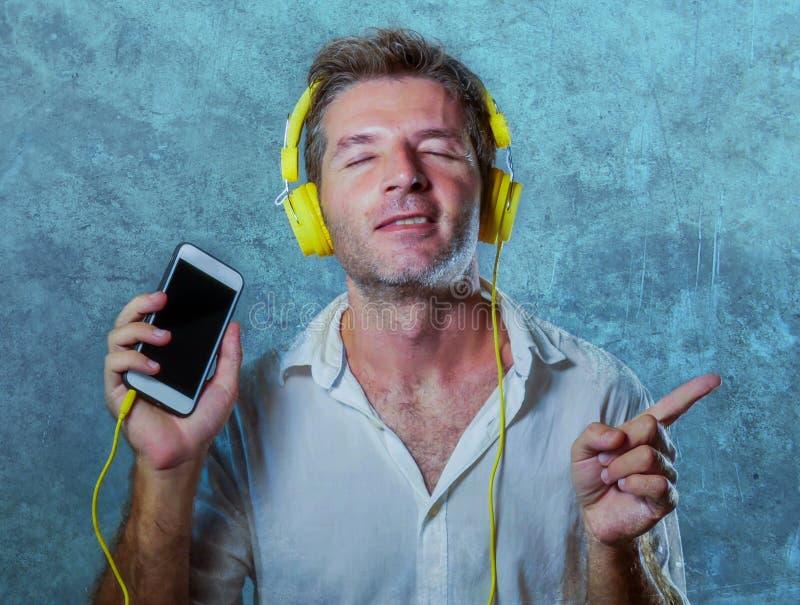 Homem fresco atrativo e feliz novo que escuta a música da música com fones de ouvido amarelos usando a dança do telefone celular  fotos de stock