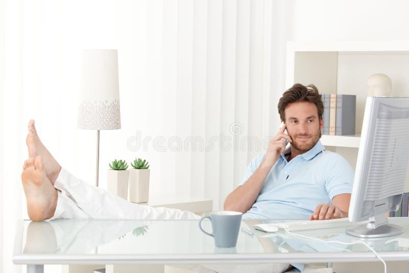 Homem fresco com pés acima na mesa