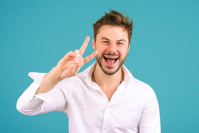 Homem fresco que mostra o sinal de v na câmera fotografia de stock royalty free