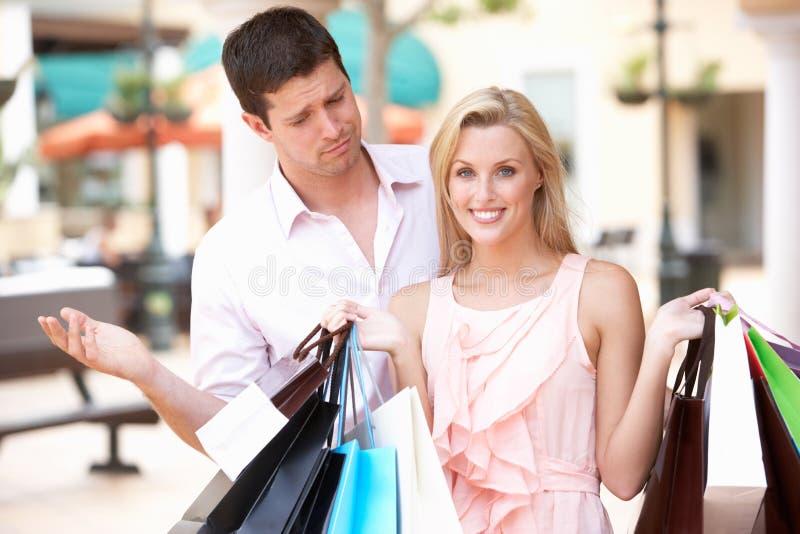 Homem frustrado com a mulher no desengate da compra fotos de stock royalty free