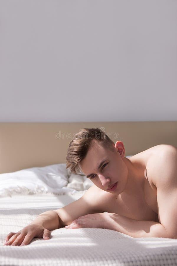 Homem frustrante que encontra-se no conceito da luta do amor da cama foto de stock