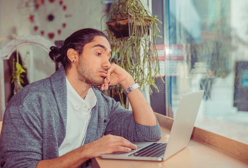 Homem furado que olha o portátil cansado fotos de stock royalty free